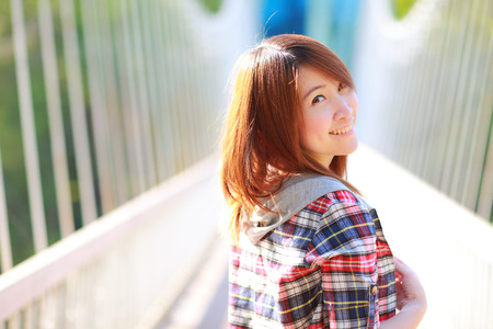 20 years old: closeup portrait of the asian girl 20 years old posing outdoors wear plaid shirt,head and shoulders ,park view in the afternoon in warm color tone