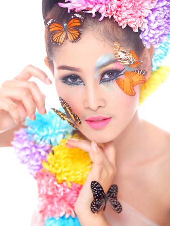 Asian Beautiful Girl With colorful make up with fresh Flowers and Butterfly  photo