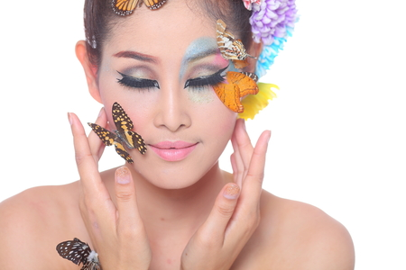 Asian Beautiful Girl With colorful make up with fresh Flowers and Butterfly  Beauty Face,head and shoulder,with white background,in studio light photo