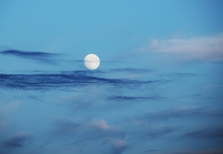 Full moon over evening sky with thin clouds Stock Photo