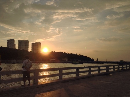 man: Man standing at the pier looking at sunset at Pattaya, Thailand