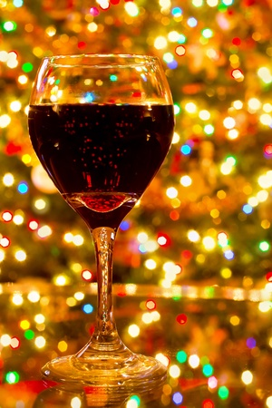 A glass of red wine with many lights glowing behind Stockfoto