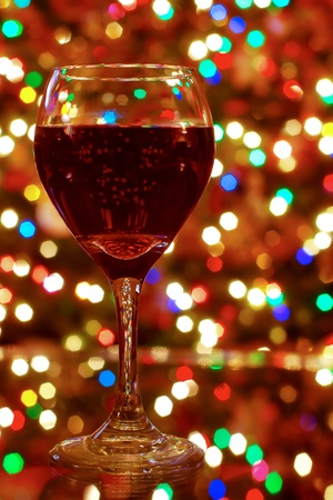 A glass of red wine with many colorful lights glowing behind photo