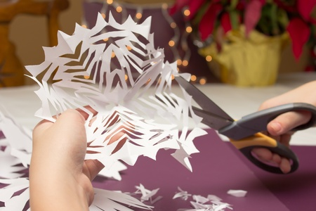 An image of hands cutting paper snowflakes.
