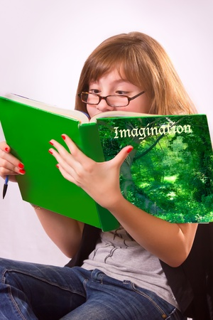 engrossed: A girl with glasses deeply engrossed in a book Stock Photo