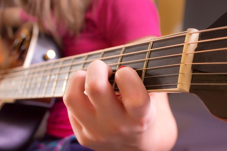 A girls hand on the neck of an acoustic guitar