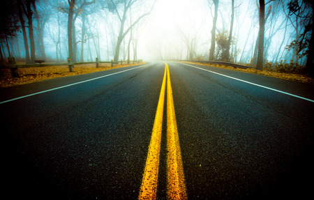 dividing lines: Yellow dividing lines leading down empty road Stock Photo