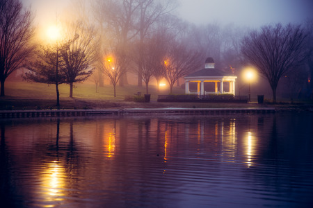 Foggy night scene at pond with lights and gazebo