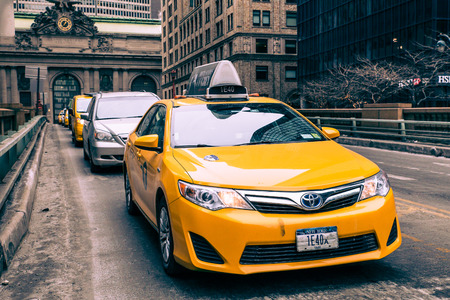 yellow taxi: NEW YORK CITY - FEBRUARY 21, 2015: View of yellow taxi and cars on Park Avenue in midtown Manhattan with Grand Central Terminal in the background.