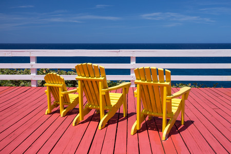 adirondack: Three adirondack chairs on a red deck overlooking the ocean