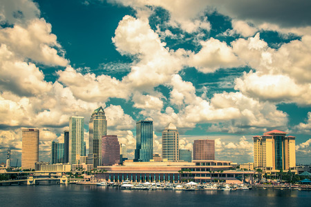 Vintage toned image of  Tampa Florida skyline with sun, clouds and reflections