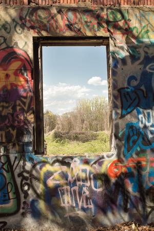 garabatos: Long Island, Nueva York, EE.UU. - 3 de mayo de 2015: escena única del paisaje visto a través de la ventana de la cubierta de edificio abandonado graffiti en el viejo Pratt Estate.