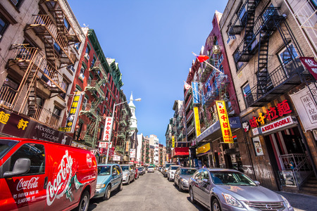 New York City, New York, USA - August 29, 2012: View of Chinatown in Manhattan with colorful signs and cars lining the street. 新闻类图片