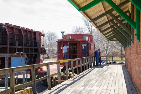 restoring: Greenport, Long Island, NY, USA - April 18, 2015: Scene of workers as they restore antique Long Island Railroad Train car at the Railroad Museum of Long Island in Greenport NY.  T