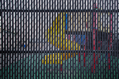 Playground equipment seen through slats of metal privacy fence 免版税图像