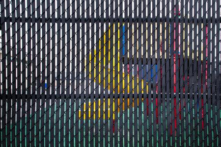 Playground equipment seen through slats of metal privacy fence Standard-Bild