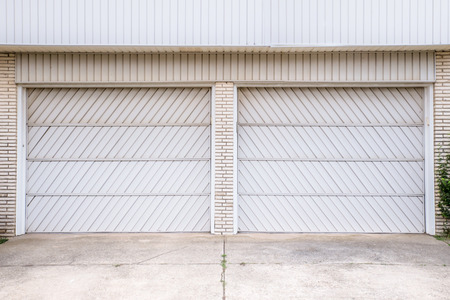 typical: typical double garage doors with aluminum siding and brick Stock Photo