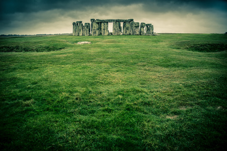 monolith: Grass field leading to Stonehenge on a cloudy gray day