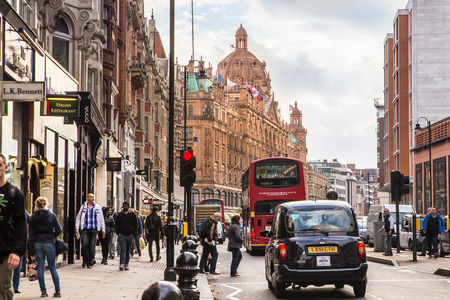 retail scene: LONDON, UNITED KINGDOM - OCTOBER 8, 2014: Street view of London along busy Brompton Road in London with Harrods and iconic double decker bus.