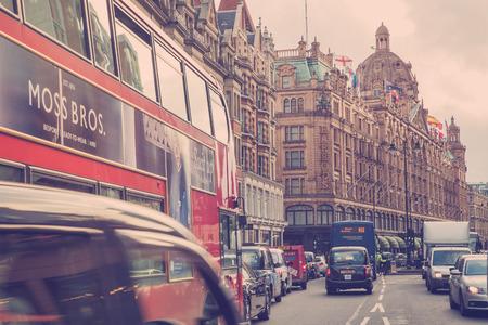 taxi: LONDRES, Reino Unido - 08 de octubre 2014: Vista de la calle del estilo del vintage de Londres junto ocupado Brompton Road, en Londres, con Harrods y emblemático autobús de dos pisos.
