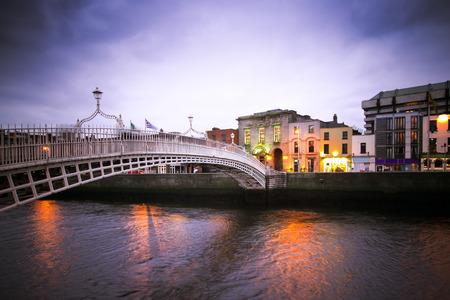 night dusk: Landmark HaPenny bridge over the River Liffey in Dublin