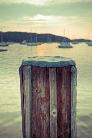piling: Vintage style image of wood pier piling with boats in the background Stock Photo