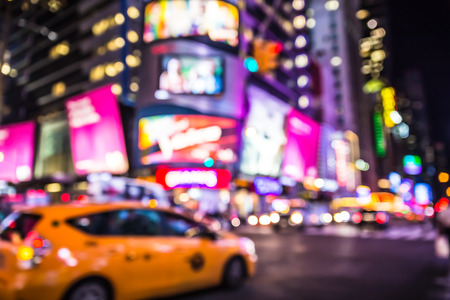 square: Defocused blur of Times Square in New York City with lights at night and taxi cab