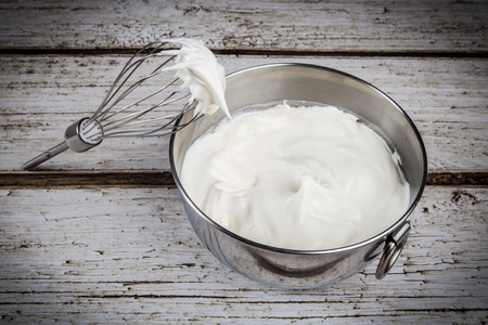 Whipped cream in bowl with and whisk