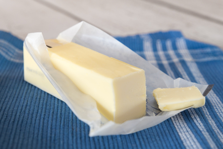 Stick of creamery butter in opened wrapper
