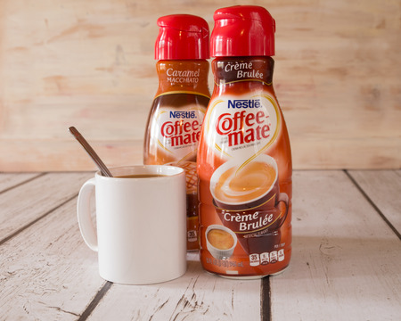 creamer: NEW YORK CITY - JANUARY 22, 2016: Two bottle of Coffee-mate liquid flavored coffee creamer and a mug of coffee.