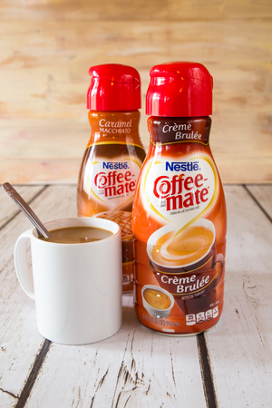 nestle: NEW YORK CITY - JANUARY 22, 2016: Two bottle of Coffee-mate liquid flavored coffee creamer and a mug of coffee.