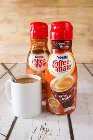 creamer: NEW YORK CITY - JANUARY 22, 2016: Two bottle of Coffee-mate liquid flavored coffee creamer and a mug of coffee.