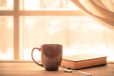 libros: Coffe y libro cerca de la ventana con la luz de sol brillante