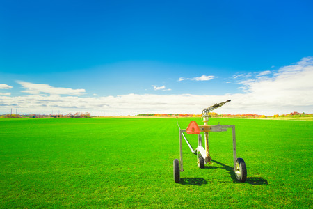 sod: Sod farm with sprinkler irrigation equipment on a sunny day Stock Photo
