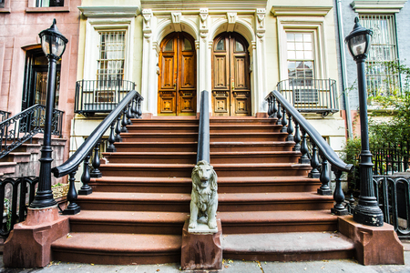 multifamily: Typical exterior steps and doors on residential homes in the Chelsea district in New York City