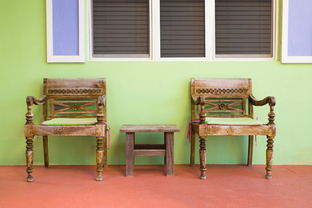 seating area: Quaint outdoor porch seating area with chairs and table in pretty topical colors Stock Photo