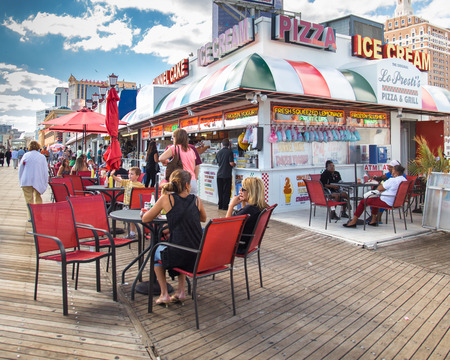 concession: ATLANTIC CITY, NJ - SEPTEMBER 22, 2013: View of food concession stand along the boardwalk at Atlantic City with people visible.