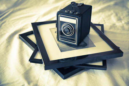 framed: vintage box camera on framed photograph with retro tone