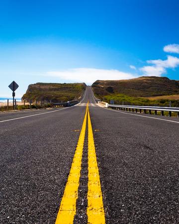 Yellow road dividing line along coastal route in California Stock Photo