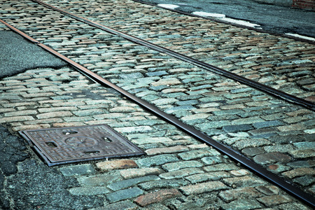 road surface: Vintage toned cobblestone street with old railroad track