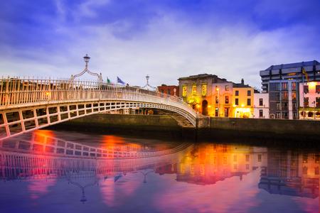 夕方にはライトや反射をアイルランドのダブリンのリフィー川のハーペニー橋 写真素材