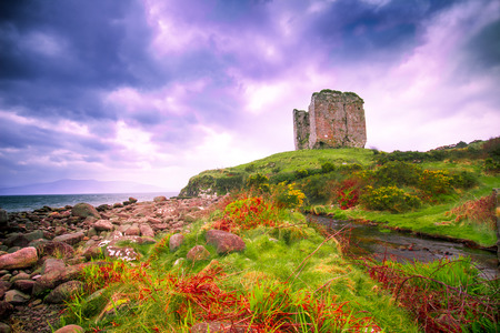 Coastal landscape along the Dingle Peninsula, County Kerry in Ireland with medieval castle ruins and dramatic sky.