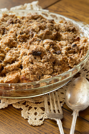 Fresh homemade dutch apple crumb dessert pie on doily with utensils