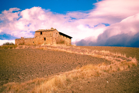 Old abandoned stone farmhouse building with path and dramatic sky from Italy countryside farm.