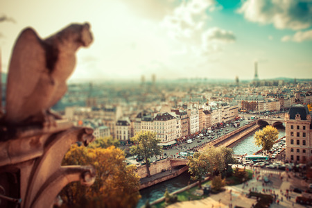 Tilt-shift miniature effect of panoramic view across Paris with gargoyle in foreground