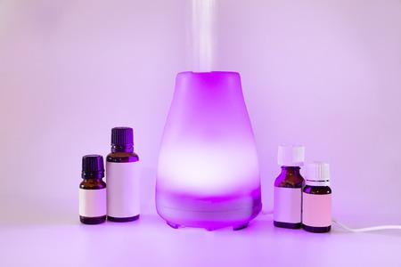 Kleurrijke aangestoken etherische olie diffuser met nevel en flessen olie Stockfoto - 71891128