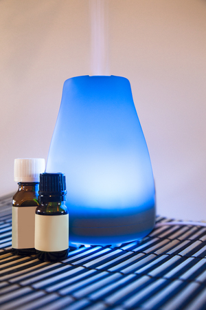 Colorful lit essential oil diffuser with mist and bottles of oils
