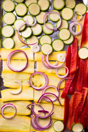 roasting pan: Rings and Slices of Raw vegetables on a pan