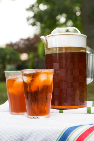 Pitcher of iced tea and two glasses in outdoor backyard summer setting