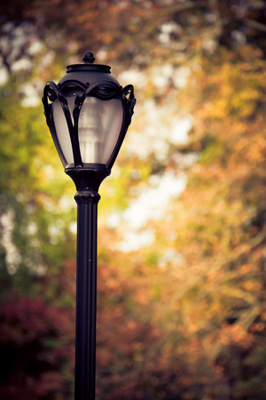 Vintage style lamp post with colorful autumn leaves in the background Stock Photo